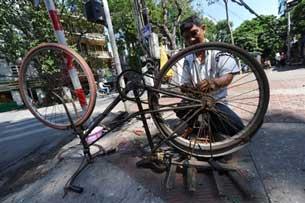Một người đàn ông sửa chữa xe đạp ở trung tâm thành phố Hà Nội, ngày 17 tháng 9 năm 2010.