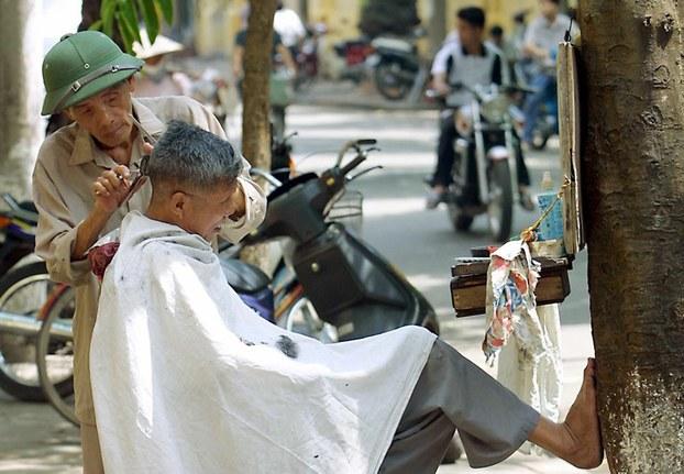 Ảnh minh họa: Người thợ hớt tóc cao tuổi vẫn còn làm việc tại Hà Nội, ảnh chụp trước đây.