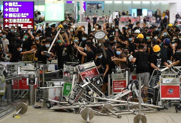 Những người biểu tình ủng hộ dân chủ chặn lối vào nhà ga sân bay sau vụ ẩu đả với cảnh sát tại sân bay quốc tế Hong Kong vào cuối ngày 13 tháng 8 năm 2019.
