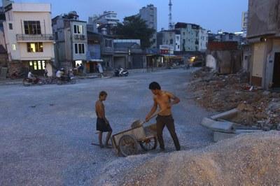 Hai công nhân dọn dẹp vật liệu xây dựng khu vực đường sắt Cát Linh - Hà Đông, hôm 12/5/2012.