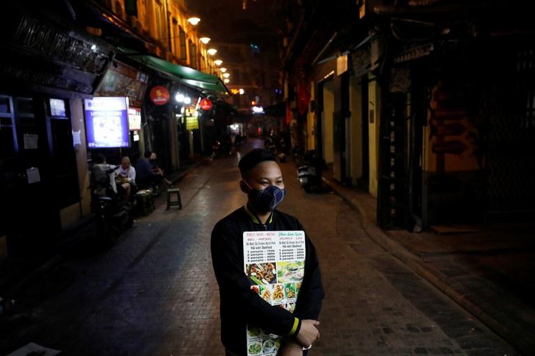 Nhân viên ở một nhà hàng tại Hà Nội cầm bảng quảng cáo trong thời kỳ dich bệnh.