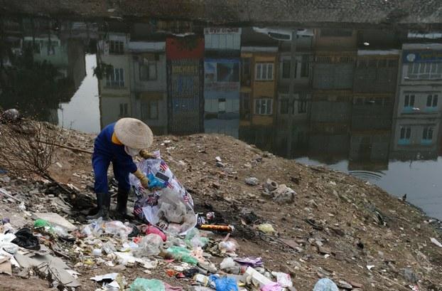 Ảnh minh họa. Một công nhân môi trường thu gom rác và các vật phẩm  tái chế dọc theo kênh Tô Lịch, ở Hà Nội. Hình chụp ngày 18/2/13.