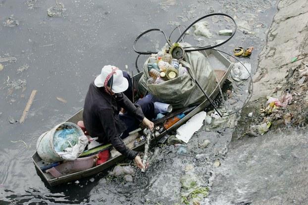 Hình minh hoạ. Một người nhặt rác đang lượm những đồ có thể tái chế tại một con kênh ô nhiễm nặng ở Hà Nội hôm 20/10/2006