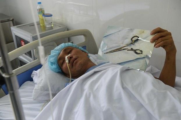 Ông Ma Văn Nhật với chiếc kéo được lấy ra từ bụng ông sau 18 năm. Ảnh chụp hôm 4/1/2017 tại một bệnh viện ở Thái Nguyên vào ngày 4 tháng 1 năm 2017.