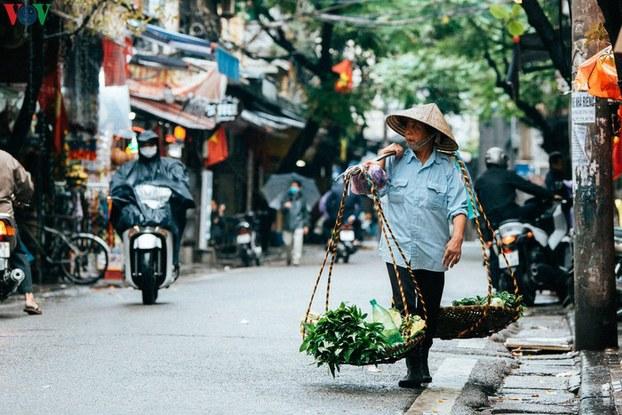 Một phụ nữ gánh rau bán trên đường phố Hà Nội vắng vẻ trong dịch COVID-19.