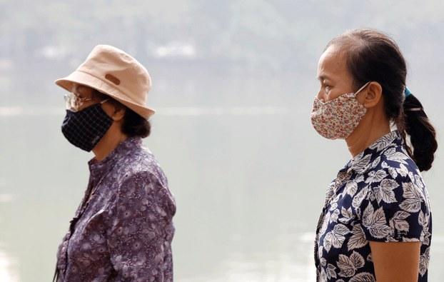 Hình minh họa. Hai người phụ nữ đeo khẩu trang khi đi ra ngoài ở Hồ Hoàn Kiếm, Hà Nội