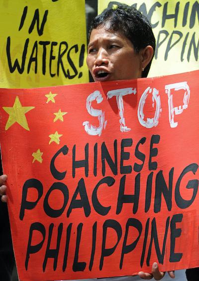 Hình minh hoạ. Một người biểu tình trước lãnh sự quán Trung Quốc ở Philippines cầm biển phản đối nạn đánh bắt cá lậu của Trung Quốc ở Biển Đông hôm 11/4/2013