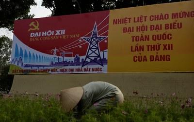 Hình minh họa. Một công nhân đang chăm vườn hoa ngay trước tấm biển chào mừng đại hội đảng ở Hà Nội hôm 8/1/2016