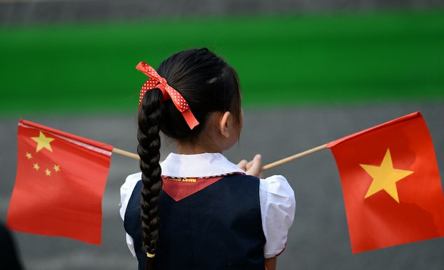 Hình minh hoạ. Một em học sinh Việt Nam cầm cờ Trung Quốc và Việt Nam tại lễ đón Chủ tịch Trung Quốc Tập Cận Bình ở Hà Nội hôm 12/11/2017