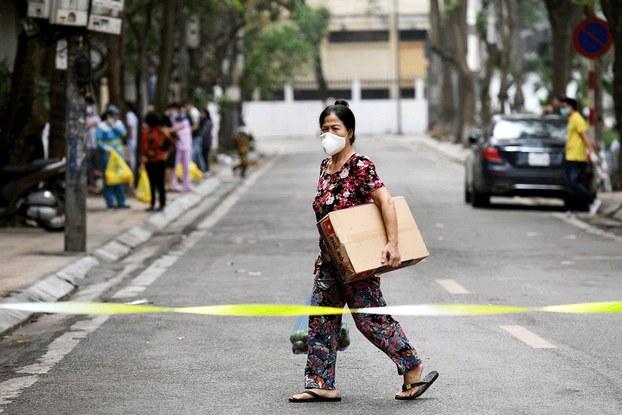 Hình minh họa. Một phụ nữ đeo khẩu trang đi trong khu vực phố Trúc Bạch bị phong tỏa sau trường  hợp thứ 17 và 21 nhiễm COVID - 19 ở Hà Nội hôm 8/3/2020