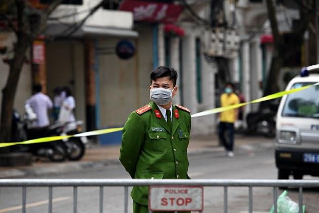 Hình minh hoạ. Công an đeo khẩu trang đứng canh bên ngoài điểm kiểm soát khu vực cách ly ở Trúc Bạch, Hà Nội hôm 8/3/2020