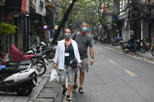 Hình minh hoạ. Khách du lịch đeo khẩu trang đi bộ trên phố ở Hà Nội hôm 17/3/2020