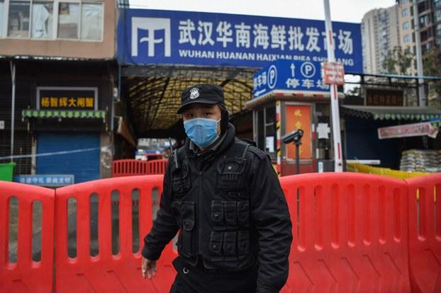Hình minh họa. Một cảnh sát đứng canh ngoài chợ hải sản ở Vũ Hán, nơi được cho là phát sinh coronavirus.