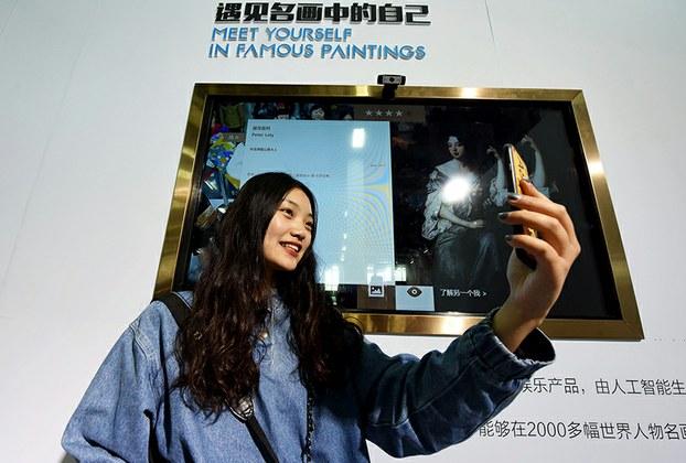 Một phụ nữ Trung Quốc đang thử sản phẩm nhận diện khuôn mặt tại một hội chợ ở Hàng Châu. Hình chụp ngày 26/04/17.