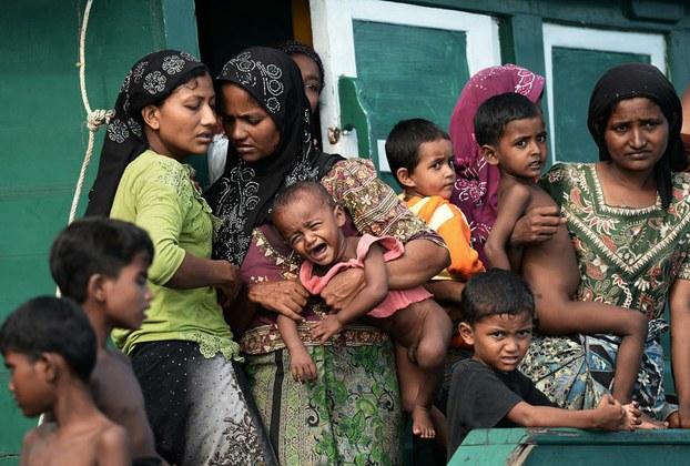 Hình ảnh cho thấy phụ nữ di cư Rohingya bế con đứng trên một chiếc thuyền trôi dạt trên vùng biển Thái gần đảo Koh Lipe ở Andaman vào ngày 14 Tháng 5 năm 2015
