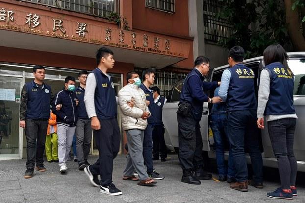 Hình minh hoạ. Nhân viên xuất nhập cảnh Đài Loan dẫn 3 người đàn ông (đeo khẩu trang) bị cho là nằm trong số 152 khách Việt bỏ trốn sau khi đến Đài Loan. Hình chụp hôm 28/12/2018 ở Đài Bắc.