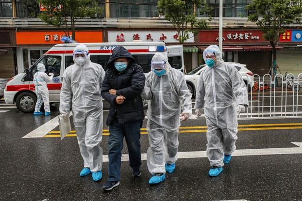 Hình minh họa. Hình chụp hôm 26/1/2020: nhân viên y tế mặc đồ bảo hộ đi cùng một bệnh nhân vào một bệnh viện ở Vũ Hán