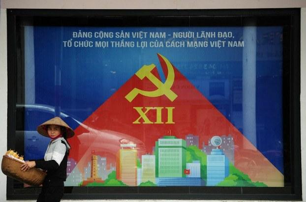 Một người bán hàng rong đi qua một tấm áp phích tuyên truyền cho Đại hội toàn quốc Đảng Cộng sản Việt Nam trên đường phố Hà Nội ngày 15 tháng 1 năm 2016.