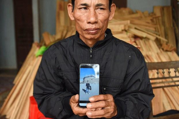 Hình minh họa. Ông Nguyễn  Đình Gia cầm điện thoại có hình con trai Nguyễn Đình Lượng, 20 tuổi, người đã mất tích khi tìm đường vào Anh