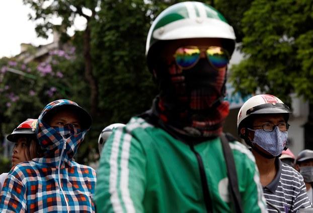 Người dân đeo khẩu trang khi lái xe ở đường phố Hà Nội ngày 21/5/2018.