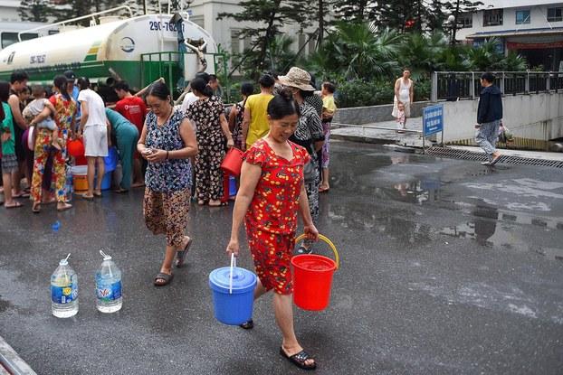 Hình minh họa. Người Hà Nội đi lấy nước miễn phí do nguồn nước máy bị nhiễm dầu