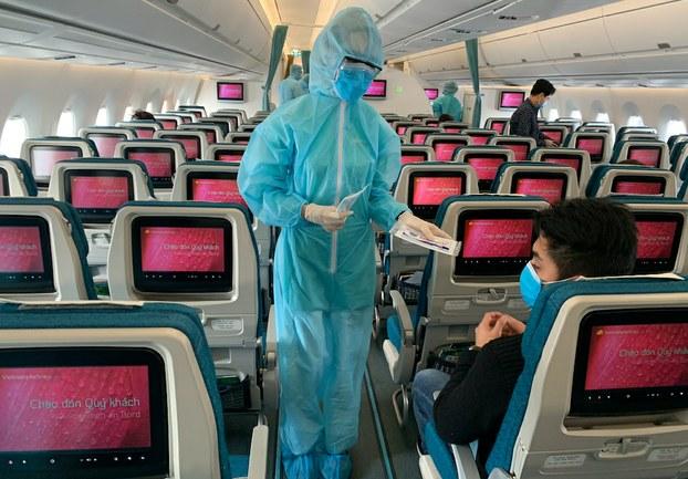 Hình minh hoạ. Hình chụp hôm 18/3/2020: nhân viên hãng hàng không Vietnam Airlines trong trang phục bảo vệ chống lây nhiễm COVID-19 phục vụ hành khách trên chuyến bay giữa Châu Âu và Việt Nam
