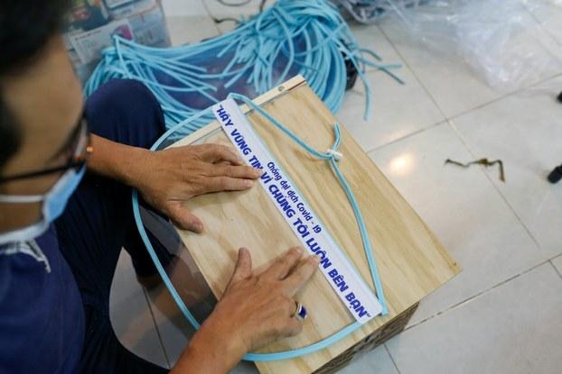 Hình minh hoạ. Người đàn ông đang dán nhãn lên khẩu trang nhựa trong mùa dịch COVID-19. Hình chụp hôm 5/4/2020 ở TP Hồ Chí Minh