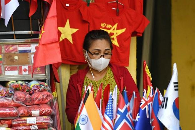 Hình minh hoạ. Một phụ nữ đeo khẩu trang bán hàng lưu niệm trên phố ở Hà Nội hôm 26/2/2020