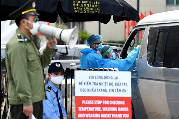 Hình minh hoạ. Nhân viên y tế kiểm tra thân nhiệt người vào cổng bệnh viện Bạch Mai, Hà Nội hôm 24/3/2020