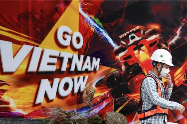 Một công nhân đeo khẩu trang đi ngang qua bảng quảng cáo cho cuộc đua Formula One Vietnam Grand Prix hôm 10/3/2020.