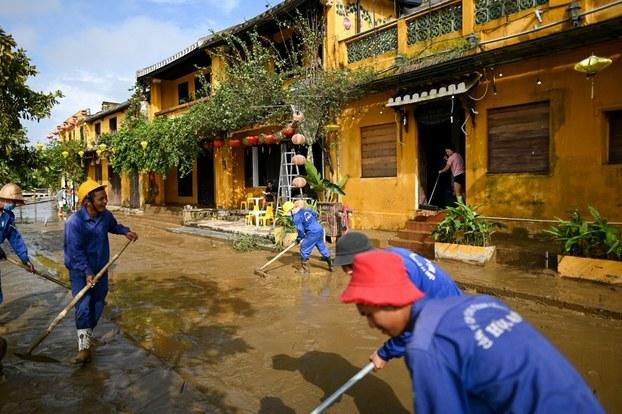Công nhân và người dân dọn dẹp đường phố ngày 30 tháng 10 năm 2020, sau khi nước rút tại phố cổ Hội An, di sản thế giới được UNESCO công nhận.